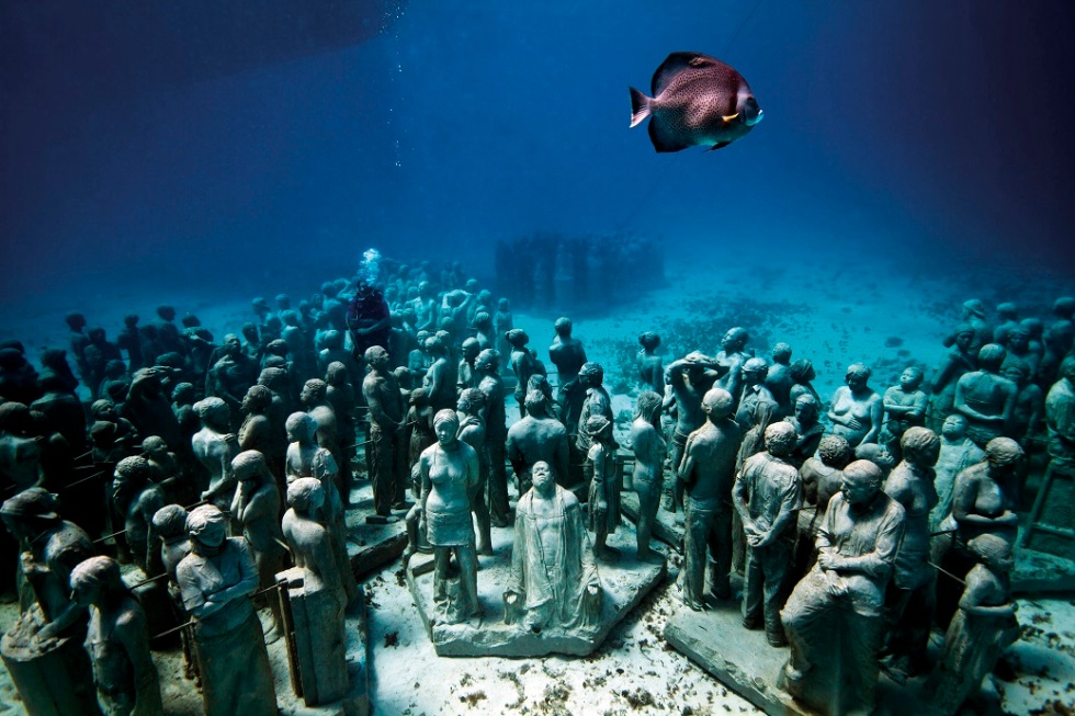 CANCUN, MEXICO - OCTOBER 4: *** EXCLUSIVE *** Fish swim past life-sized statues on the sea bed underwater at Cancun and Isla Mujeres National Marine Park on October 4, 2010 in Mexico. Never-before-seen pictures show the fusion of art and conservation in a brand new artificial reef supporting marine life deep underwater - made from sculptures of real members of the public. Bright tropical fish and agile divers can be seen darting in and out of the huge living art piece that contains hundreds of life-sized statues on the sea bed. Big thinking British artist Jason de Caires Taylor, 36, from Cantebury, Kent captured impressions of real people using 'life casts' and built the installation using materials that will encourage coral to grow. It will produce a coral reef and new home for a variety of aquatic creatures at the Cancun and Isla Mujeres National Marine Park in Mexico. The project, called The Museo Subacuatico de Arte (MUSA), aims to ease pressure on natural reefs in the area caused by over half a million water-going tourists who flock to the region every year. Jason's team have so far laid 350 of the 400 sculptures and are on the brink of completion. (Photo by Jason de Caires Taylor/Barcroft Media/Getty Images)