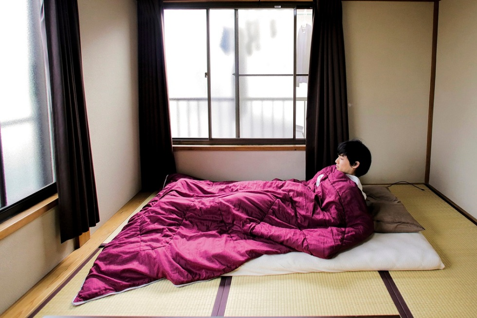 "Minimalist Katsuya Toyoda demonstrates how he sleeps in his room in Tokyo, Japan, March 5, 2016. REUTERS/Thomas Peter SEARCH ""MINIMALISM"" FOR THIS STORY. SEARCH ""THE WIDER IMAGE"" FOR ALL STORIES - RTX2H2QQ"